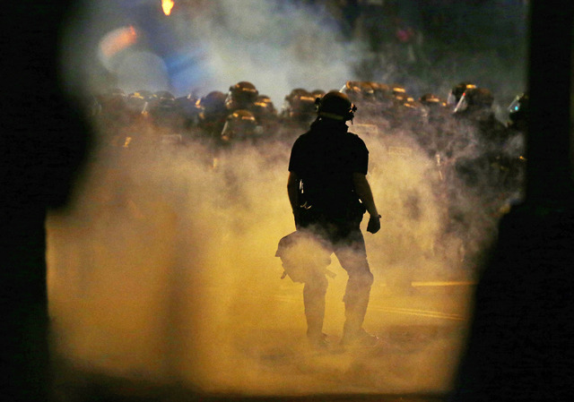Police fire teargas as protestors converge on downtown following Tuesday's police shooting of Keith Lamont Scott in Charlotte, N.C., Wednesday, Sept. 21, 2016. Protesters have rushed police in rio ...