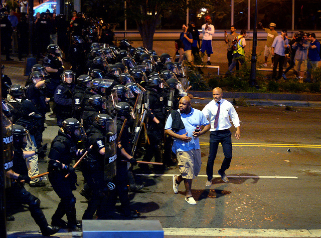 Charlotte-Mecklenburg police officers begin to push protesters from the intersection near the Epicentre in Charlotte, N.C. Wednesday, Sept. 21, 2016.  Authorities in Charlotte tried to quell publi ...