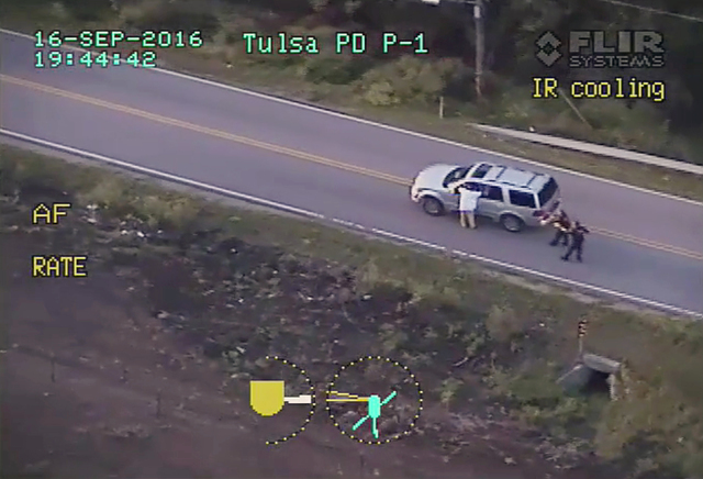 In a frame from video, Terence Crutcher, left, with his arms up, is pursued by police officers as he walks next to his stalled SUV moments before he was shot and killed by one of the officers in T ...