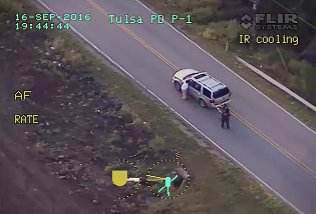 In a frame from video, Terence Crutcher, left, lowers his right arm as he is pursued by police officers moments before he was shot and killed by one of the officers in Tulsa, Okla., Tuesday, Sept. ...