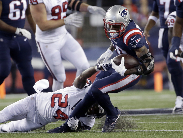 New England Patriots wide receiver Malcolm Mitchell (19) breaks the grasp of Houston Texans cornerback Johnathan Joseph (24) during the first half of an NFL football game Thursday, Sept. 22, 2016, ...