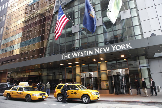 FILE - In this Wednesday, Feb. 1, 2012, file photo, a man hails a taxi in front of the Westin New York hotel, in New York. Marriott International closed early Friday, Sept. 23, 2016, on its acquis ...