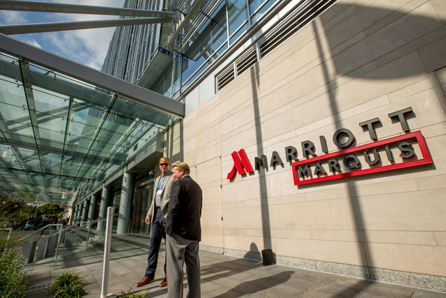 FILE - In this Wednesday, Oct. 14, 2015, file photo, two men stand outside the newly-built Marriott Marquis hotel in Washington. Marriott International closed early Friday, Sept. 23, 2016, on its  ...