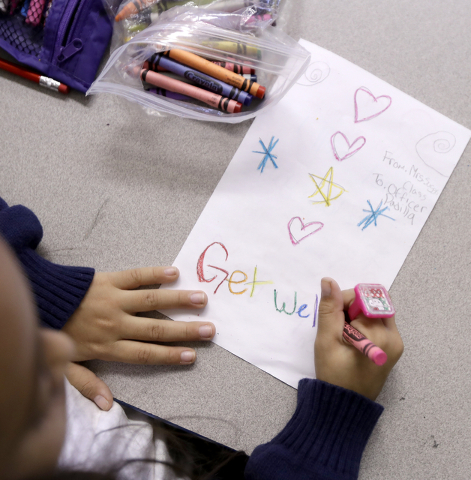 Arianna Cestona, a third grade student at Linden School No. 5, makes a card for Linden Police officer Angel Padilla, Thursday, Sept. 22, 2016, in Linden, N.J. Padilla, who was injured in a shootou ...