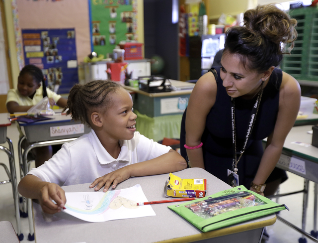 Roxy Suggs, right, a third grade teacher at Linden School No. 5, talks to Mya Austin during a class assignment making cards for Linden Police officer Angel Padilla, Thursday, Sept. 22, 2016, in Li ...
