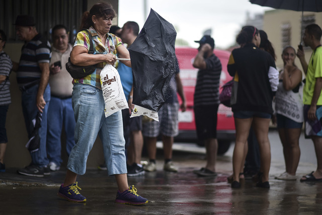 A woman carries a bag of ice that she bought at El Angel Ice Plant during a massive blackout in San Juan, Puerto Rico, Thursday, Sept. 22, 2016. Puerto Ricans faced another night of darkness Thurs ...