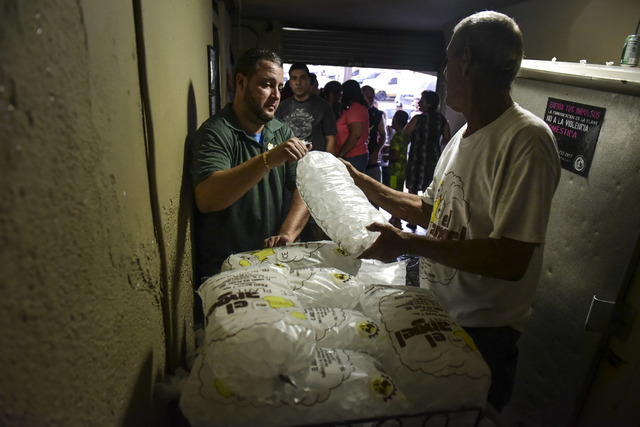 People buy ice during a massive blackout in San Juan, Puerto Rico, Thursday, September 22, 2016. Puerto Ricans faced another night of darkness Thursday as crews slowly restored electricity a day a ...