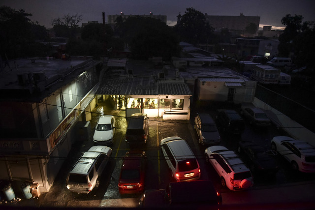 Motorists illuminate a storefront with their headlights as they drive in to buy bread after a massive blackout, in San Juan, Puerto Rico, Thursday, Sept. 22, 2016.  (Carlos Giusti/AP)