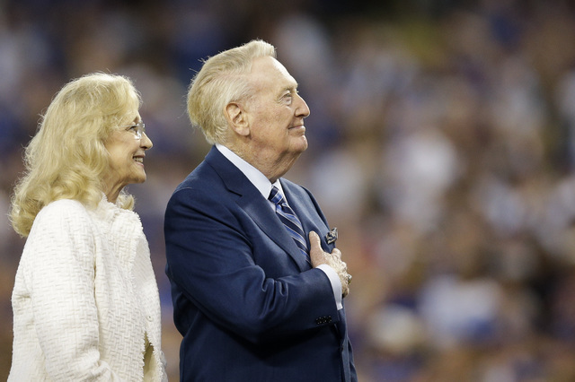 Hall of Fame Los Angeles Dodgers broadcaster Vin Scully places his hand over his heart as he is joined by wife Sandi during Vin Scully Appreciation Day before the team's baseball game against the  ...