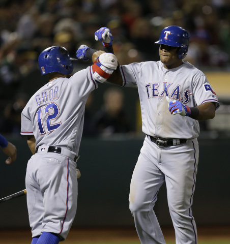 Texas Rangers' Adrian Beltre, right, celebrates with Rougned Odor (12) after hitting a two-run home run against the Oakland Athletics in the seventh inning of a baseball game Friday, Sept. 23, 201 ...