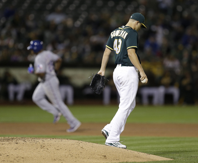 Oakland Athletics pitcher Kendall Graveman, right, walks off the mound after giving up a two run home run to Texas Rangers' Adrian Beltre, left, in the seventh inning of a baseball game Friday, Se ...