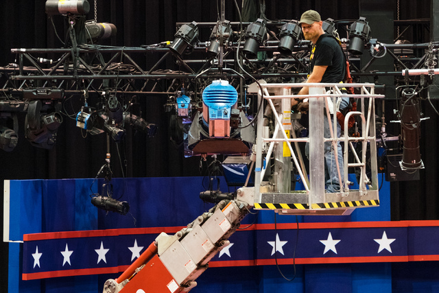 A technician examines the lighting grid as preparations continue for Monday's first debate presidential between Democratic Hillary Clinton and Republican Donald Trump, Saturday, Sept. 24, 2016, at ...