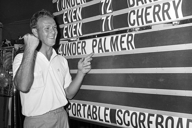 This June 19, 1960, file photo shows Arnold Palmer pointing to his name on the press tent scoreboard showing his four-under-par total, for 72 holes, during the National Open golf tournament at the ...