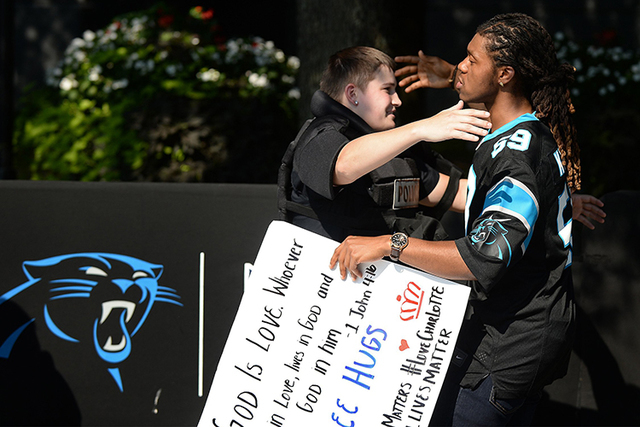 JaGerran Knight reaches out to hug a Charlotte-Mecklenburg police officer at Bank of America Stadium, where protesters gathered for the the Carolina Panthers-Minnesota Vikings game on Sunday. (Die ...