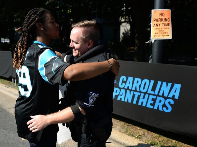JaGerran Knight, of Charlotte, N.C., left, reaches out to hug a police officer at Bank of America Stadium, where people protested prior to an NFL football game between the Minnesota Vikings and th ...