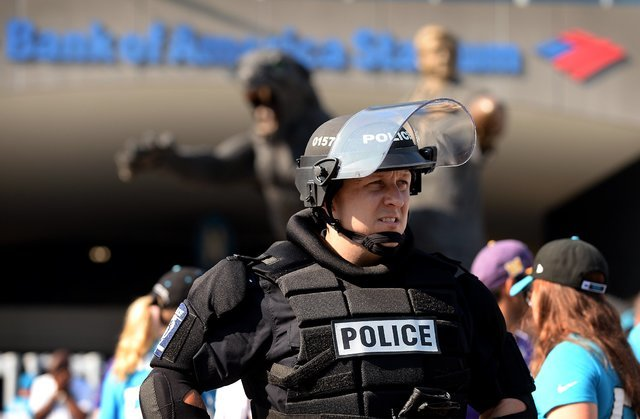 A Charlotte-Mecklenburg police officer in riot gear watches foot traffic pass an entrance area at Bank of America Stadium, where people were protesting, prior to an NFL football game between the M ...