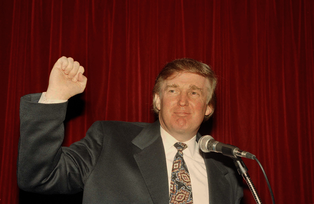 In this Dec. 21, 1994 file photo, Donald Trump raises his fist at a news conference in New York where he denounced a report that the Sultan of Brunei was interested in buying the Plaza, the landma ...