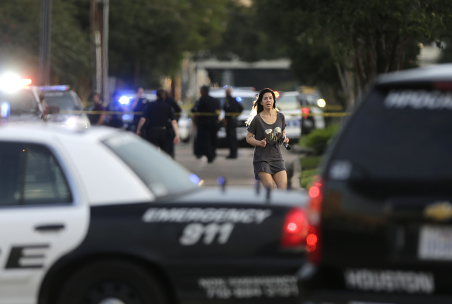 Jennifer Molleda runs down Wesleyan Street in Houston to find her husband, Alan Wakim, who had two bullets whiz by his face after going through his windshield on the way to work along Wesleyan at  ...