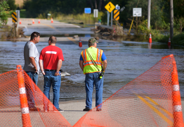 Mike Baer, left, Brad O'Donnell and Todd Huxford stand near the edge of the flooded Le Sueur River across Park Street North Saturday, Sept. 24, 2016, in St. Clair, Minn. (Bre McGee/The Free Press  ...