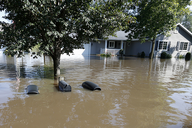 The tops of mailboxes barely break the surface of floodwater from the Cedar River in the North Cedar neighborhood of Cedar Falls, Iowa, Saturday, Sept. 24, 2016. (Brandon Pollock/The Courier via AP)