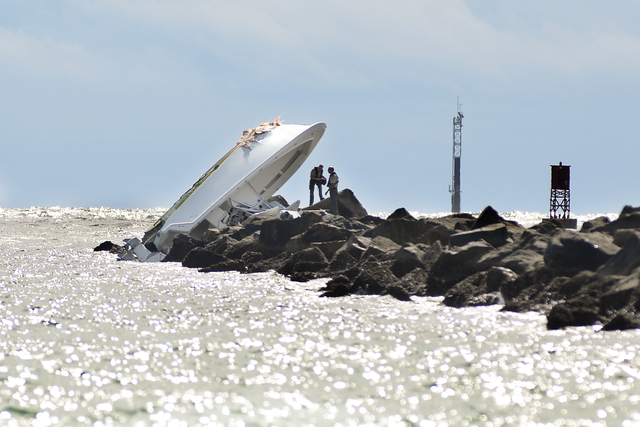 Investigators inspect an overturned boat as it rests on a jetty after a crash, Sunday, Sept. 25, 2016, off Miami Beach, Fla. Authorities said that Miami Marlins starting pitcher Jose Fernandez was ...