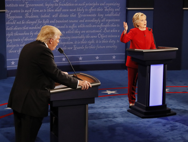 Republican presidential nominee Donald Trump and Democratic presidential nominee Hillary Clinton speak at the same time during the presidential debate at Hofstra University in Hempstead, N.Y., Mon ...