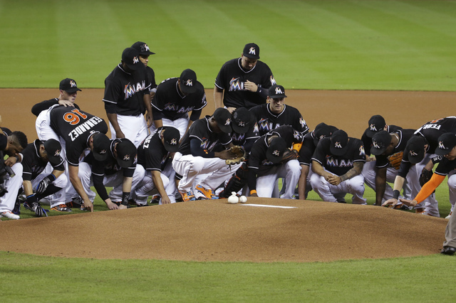 Miami Marlins players wearing a jersey in honor of pitcher Jose Fernandez (16) gather around the pitching mound before a baseball game against the New York Mets, Monday, Sept. 26, 2016, in Miami.  ...