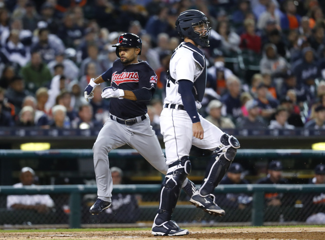Cleveland Indians' Coco Crisp scores as Detroit Tigers catcher James McCann waits for the throws on a Roberto Perez single during the eighth inning of a baseball game in Detroit, Monday, Sept. 26, ...
