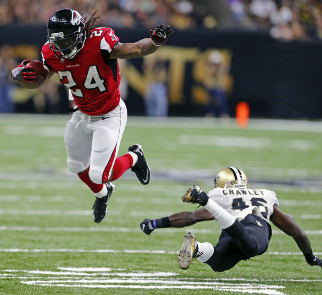 Atlanta Falcons running back Devonta Freeman (24) tries to avoid the tackle by New Orleans Saints cornerback Ken Crawley (46) in the first half of an NFL football game in New Orleans, Monday, Sept ...