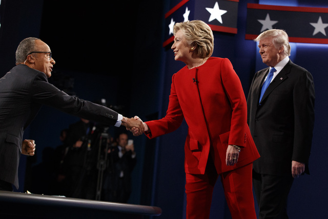 Democratic presidential candidate Hillary Clinton shakes hands with moderator Lester Holt as Republican presidential candidate Donald Trump watches Monday at Hempstead, New York. (Evan Vucci/AP)