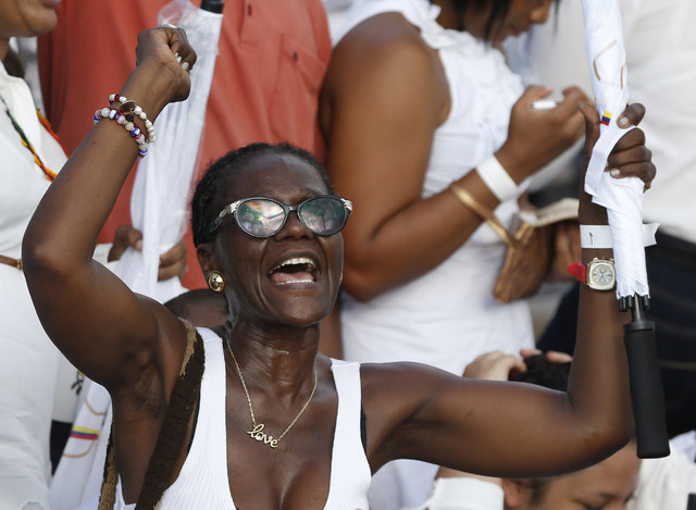 A woman shouts slogans in support of the peace agreement prior the signing of the peace agreement between Colombia's government and the Revolutionary Armed Forces of Colombia, FARC, in Cartagena ...