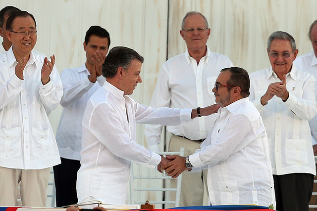 Colombia's President Juan Manuel Santos, front left, and the top commander of the Revolutionary Armed Forces of Colombia (FARC) Rodrigo Londono, known by the alias Timochenko, shake hands after  ...
