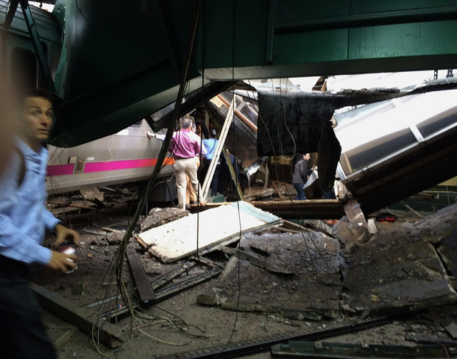 In a photo provided by William Sun, people examine the wreckage of a New Jersey Transit commuter train that crashed into the train station during the morning rush hour in Hoboken,, N.J., Thursday, ...