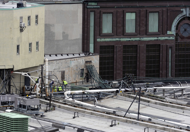 Workers examine a section of the roof at the Hoboken station where a train crashed into the building, killing Fabiola Bittar de Kroon. (Joe Epstein/AP)