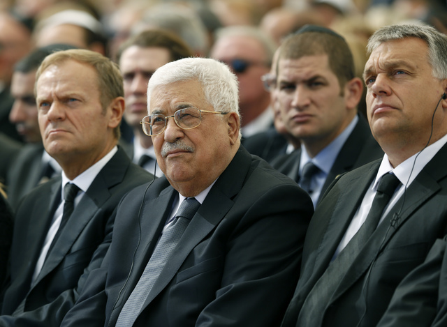 Palestinian President Mahmoud Abbas, center, sits alongside European Council President Donald Tusk, left, as they attend the funeral of former Israeli President Shimon Peres, 93, on Mt. Herzl Ceme ...