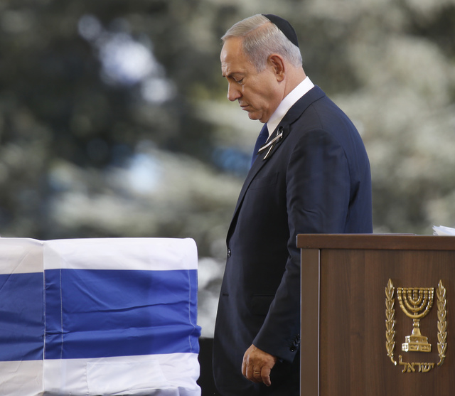 Israeli Prime Minister Benjamin passes the flag-draped coffin of former Israeli President Shimon Peres after speeching during his funeral at the Mount Herzel national cemetery in Jerusalem, Friday ...