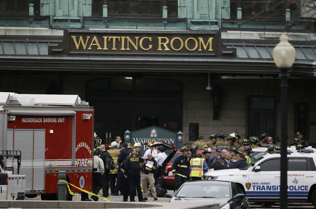 Emergency officials stand outside of the Hoboken Terminal following a train crash, Thursday, Sept. 29, 2016, in Hoboken, N.J. A commuter train crashed into the rail station during the morning rush ...