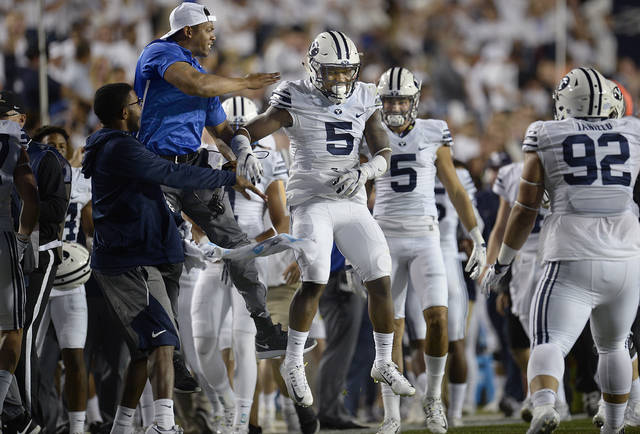 BYU defensive Dayan Lake (5) celebrates with teammates on the sideline after intercepting a Toledo pass during the first half of an NCAA college football game Friday, Sept. 30, 2016, in Provo, Uta ...