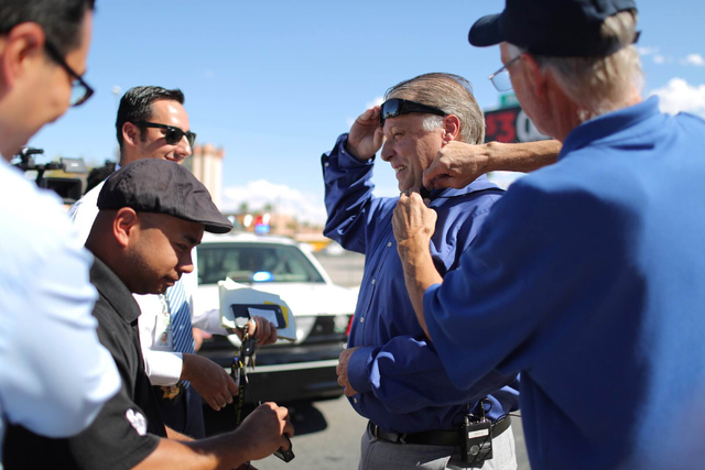 Cameramen attach microphones to Metropolitan Police Department Capt. Shawn Anderson, center, before he briefs news media members about a police chase that ended when the suspect was fatally hit by ...