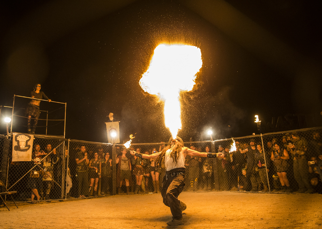 Burning Sensation blows fire in the gladiators battle cage during the seventh annual Wasteland Weekend on Friday, Sept. 23, 2016, in California City, Calif. The four day, post-apocalyptic festival ...