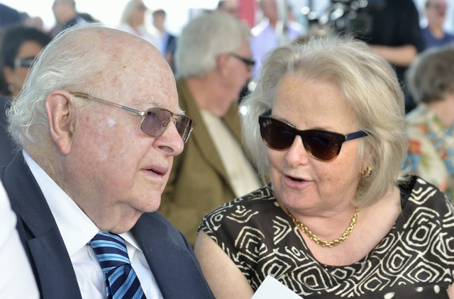 Len Ainsworth, founder and executive chairman of Ainsworth Game Technology, left, and his wife Gretel talk before the start of grand opening ceremonies for the company's new North American  ...