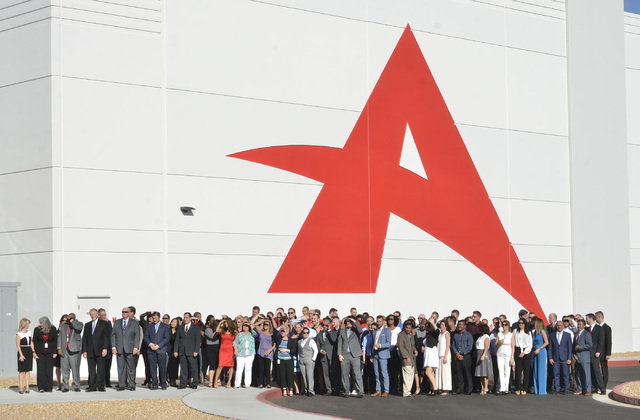 A group of people waits to have a photo taken during grand opening ceremonies for the new North American headquarters of Ainsworth Game Technology at 5800 Rafael Rivera Way in Las Vegas on Friday, ...