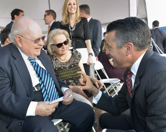 Gov. Brian Sandoval, right, talks with Len Ainsworth, founder and executive chairman of Ainsworth Game Technology, left, and Ainsworth's wife Gretel during grand opening ceremonies for the  ...