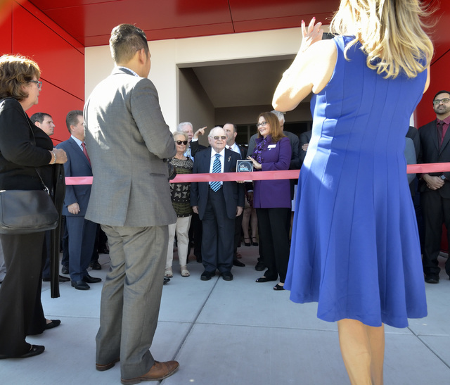 Len Ainsworth, founder and executive chairman of Ainsworth Game Technology, background center, waits for a ribbon cutting to begin during grand opening ceremonies for the company's new Nort ...