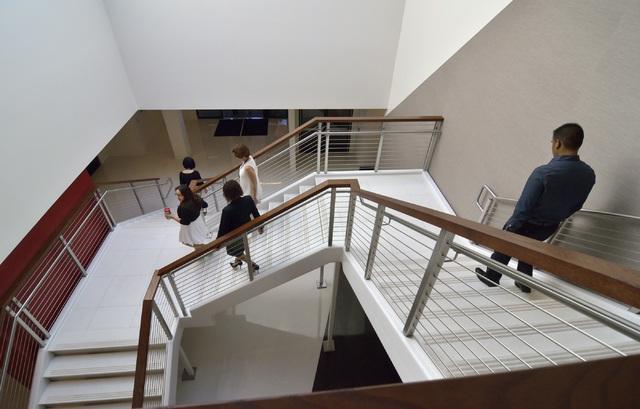 Employees head downstairs for the start of grand opening ceremonies for the new North American headquarters of Ainsworth Game Technology at 5800 Rafael Rivera Way in Las Vegas on Friday, Sept. 30, ...