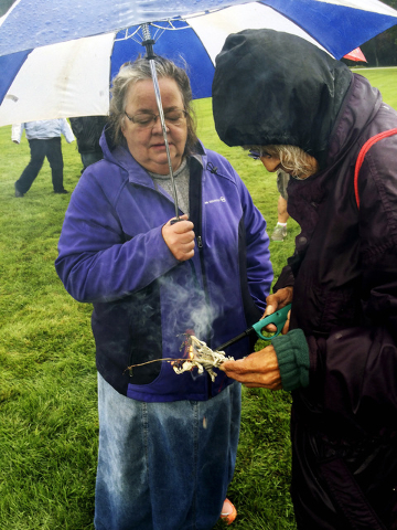 Darlene Pipeboy, right, from the Lake Traverse Reservation in South Dakota, burns sage grass during a rally of Dakota Access pipeline protesters at the North Dakota Capitol grounds Friday, Sept. 9 ...