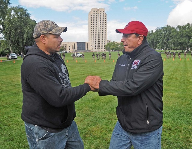 Standing Rock Sioux tribal chairman Dave Archambault II, right, greets Wayland Gray, of Muskogee Creek Hickory Ground, Okla. at the organized protest on the North Dakota state capitol grounds on F ...