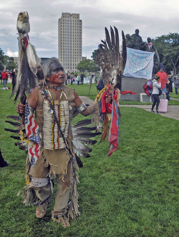 Phil Little Thunder, of Rosebud, S.D. shows his support during the protest on the grounds of the North Dakota state capitol in his pow wow regalia, Friday, Sept. 9, 2016 in Bismarck, N.D. The fede ...