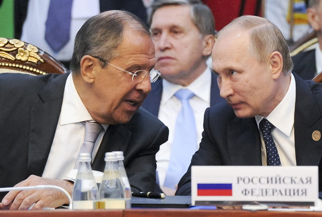 Russian President Vladimir Putin, right, and Russian Foreign Minister Sergey Lavrov speak each other at a CIS (Commonwealth of Independent States, former Soviet republics) summit in Bishkek, Kyrgy ...