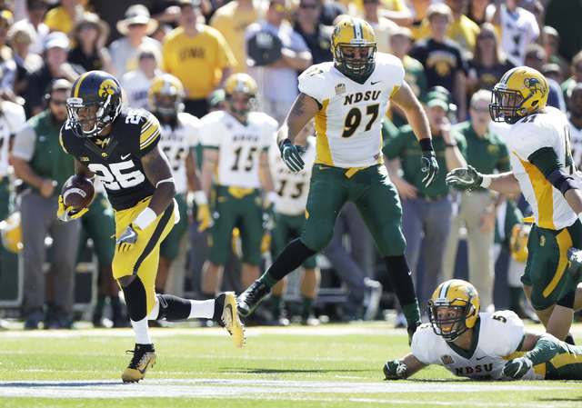 Iowa running back Akrum Wadley (25) runs from North Dakota State defenders Brad Ambrosius (97), MJ Stumpf (41) and Robbie Grimsley (5) during the first half of an NCAA college football game, Satur ...
